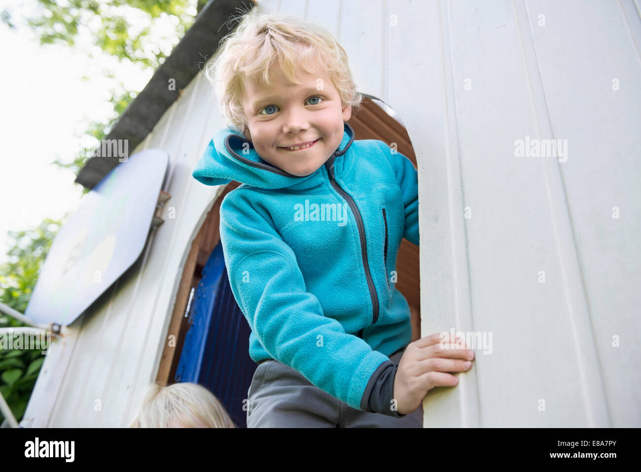 Young blonde boy playing in garden summerhouse - Stock Image
