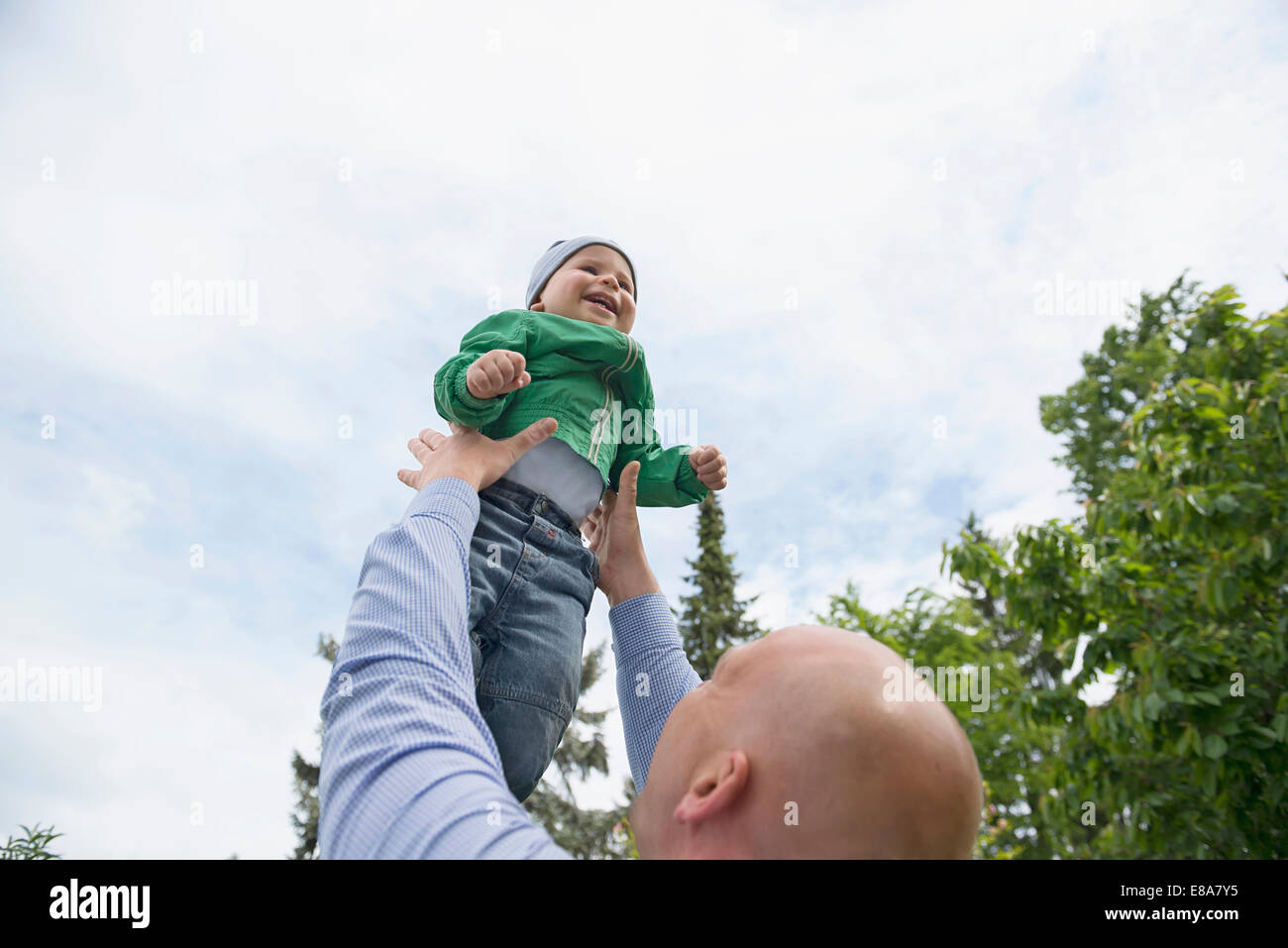 Father holding baby boy in arms playing flying - Stock Image