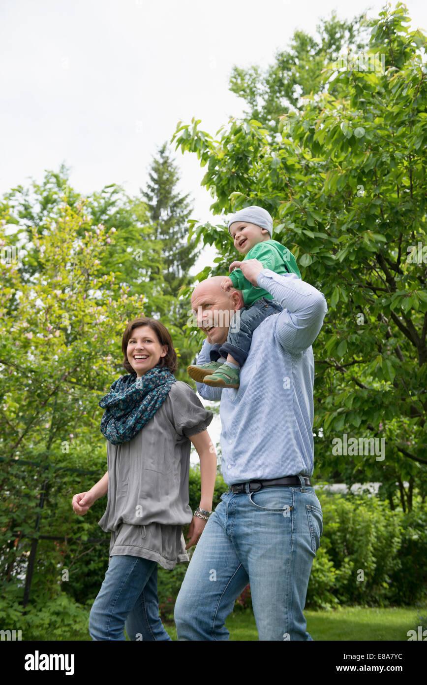 Parents mother father baby piggyback garden Stock Photo