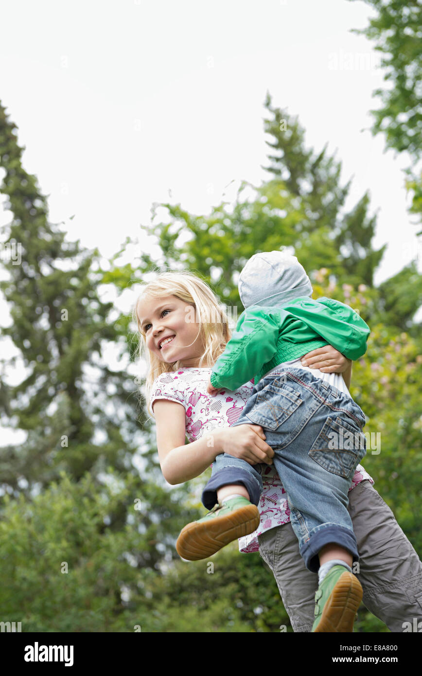 Young blonde girl carrying baby brother Stock Photo