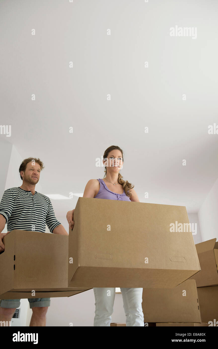 Man woman carrying boxes new home moving in - Stock Image