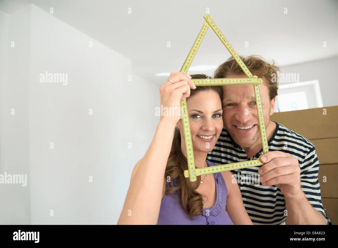 Couple holding yardstick shape house new - Stock Image