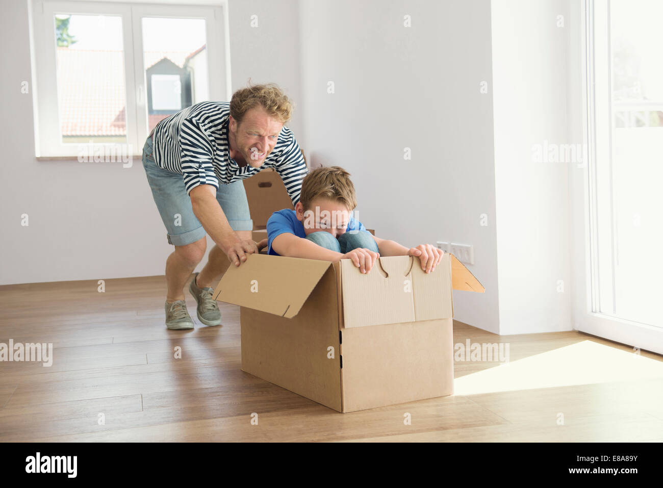 Father son new apartment playing cardboard box - Stock Image