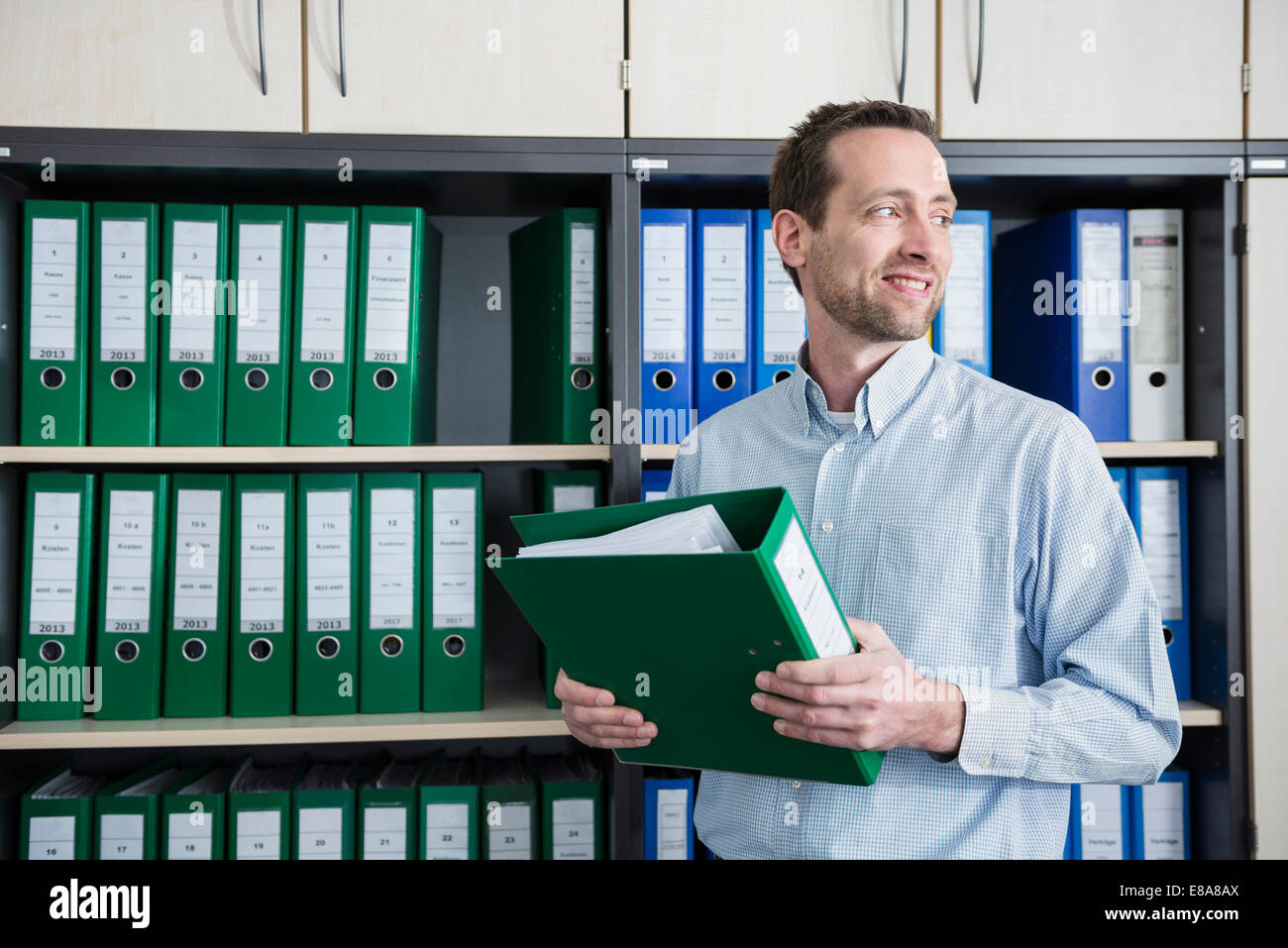 Man office sorting filing cabinet organizing - Stock Image