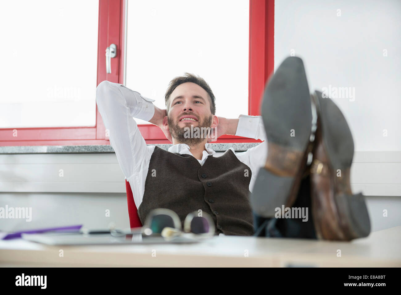 Young man office desk relaxing feet up lazy - Stock Image
