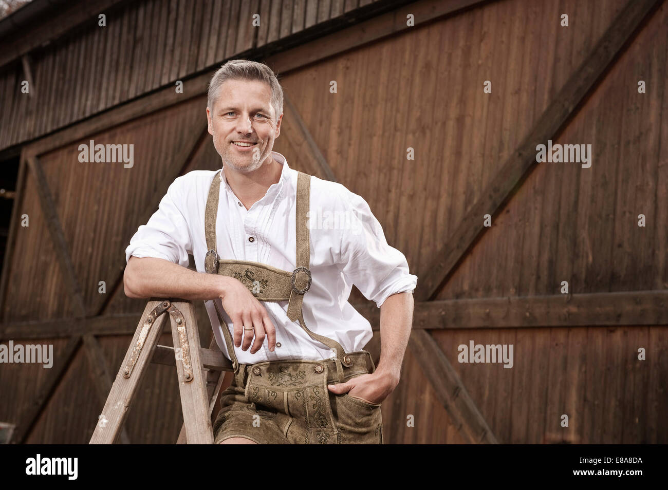 Man in lederhosen on farm, Barvaria, Germany - Stock Image