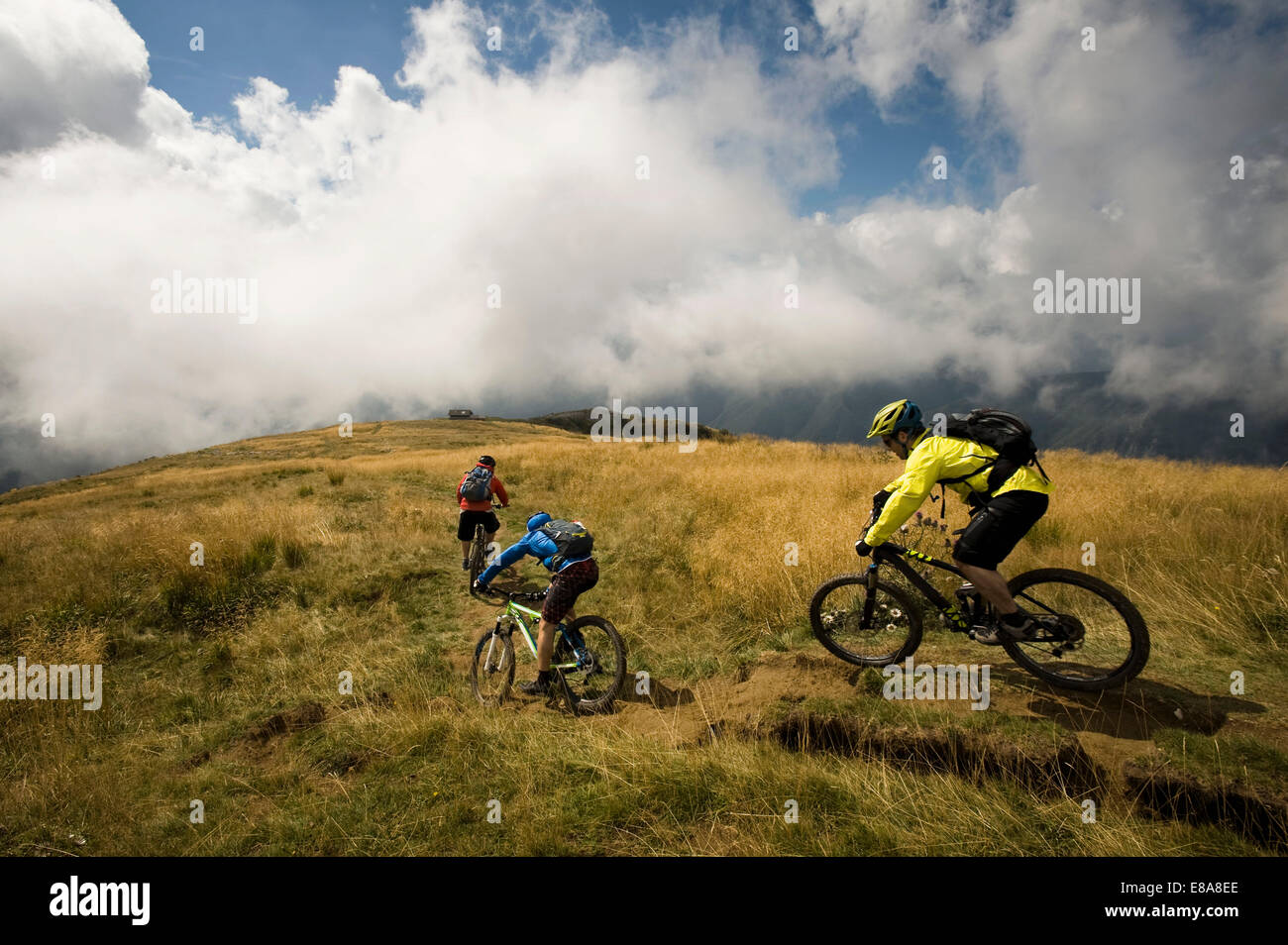 three mountain bikers on the way, Matajur, Istria, Slovenia - Stock Image
