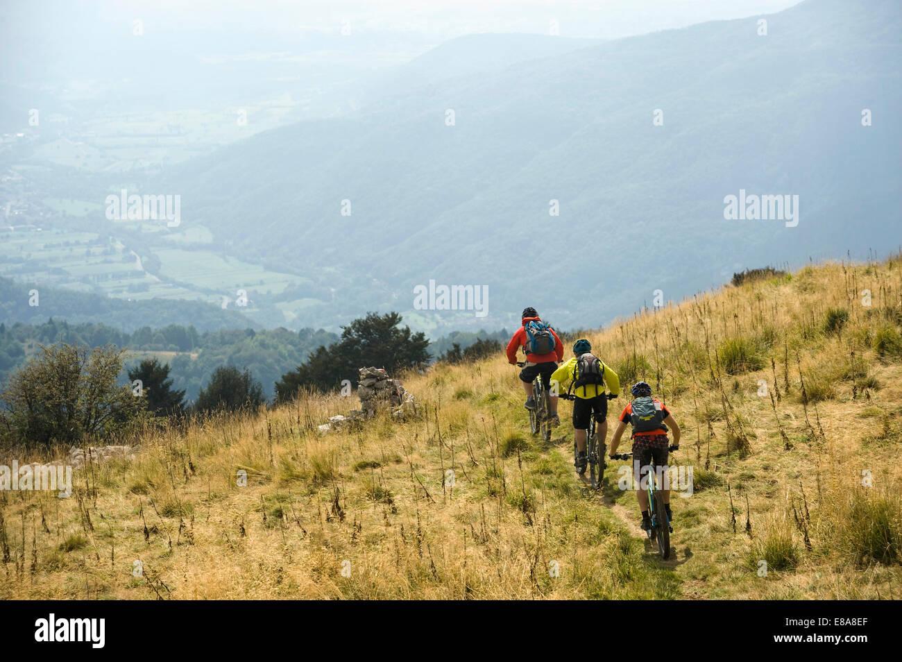 three mountain bikers on the way downhill, Matajur, Istria, Slovenia - Stock Image