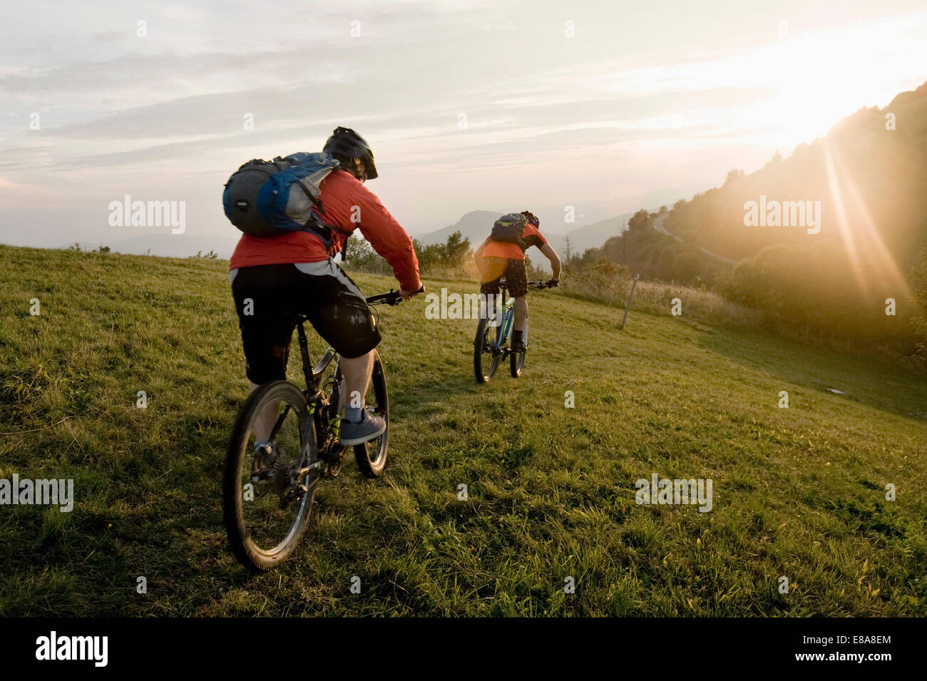 two mountain bikers on the way at sunset, Kolovrat, Istria, Slovenia - Stock Image