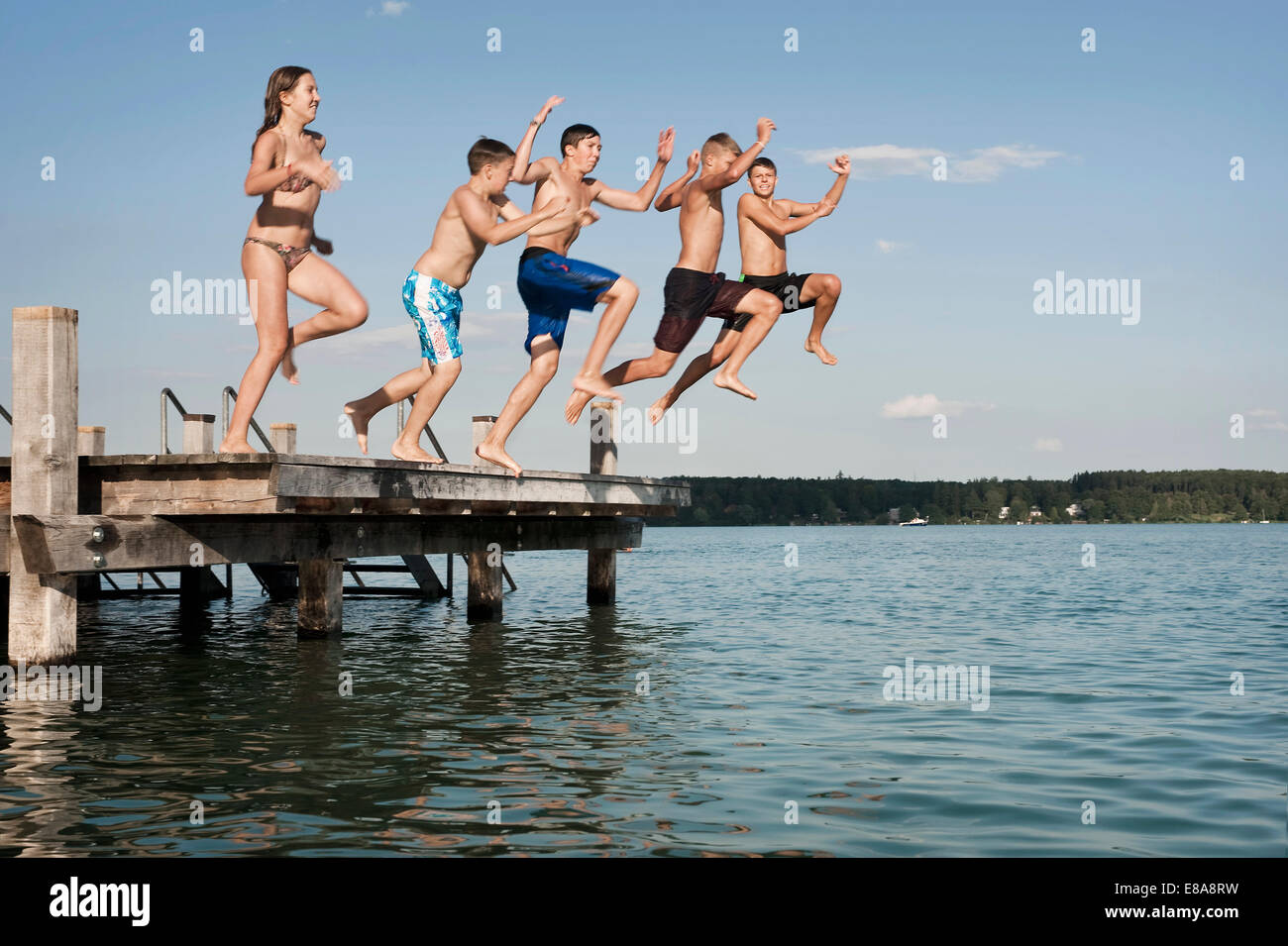 Five teenagers jumping from a jetty into lake Stock Photo