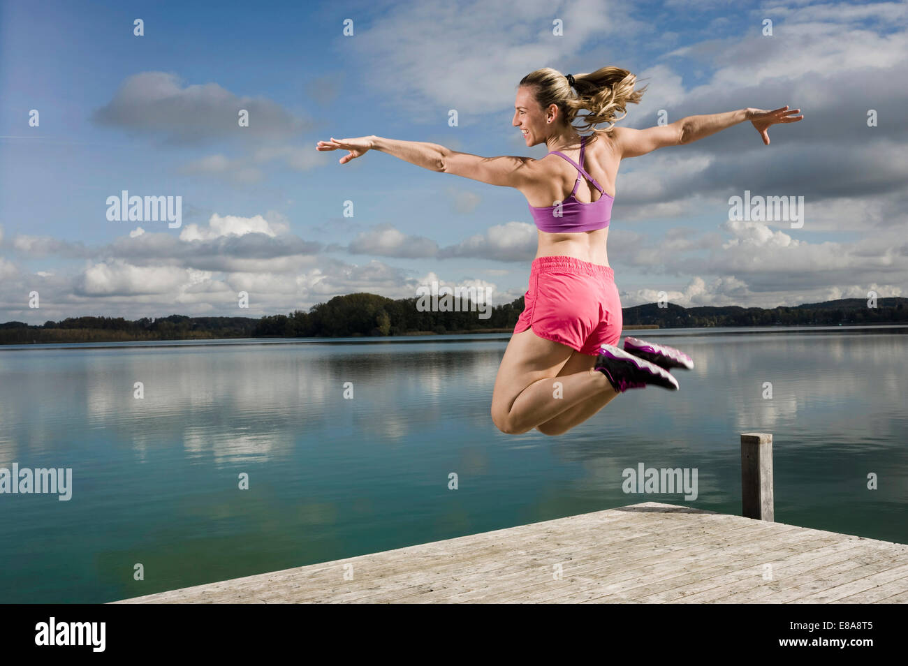 Woman jumping on jetty, Woerthsee, Bavaria, Germany - Stock Image