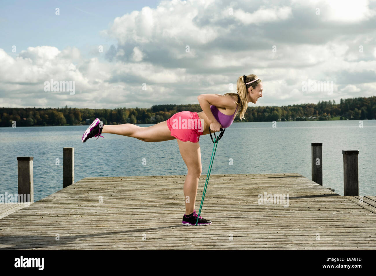 Woman woman exercising with resistance band, Woerthsee, Bavaria, Germany - Stock Image