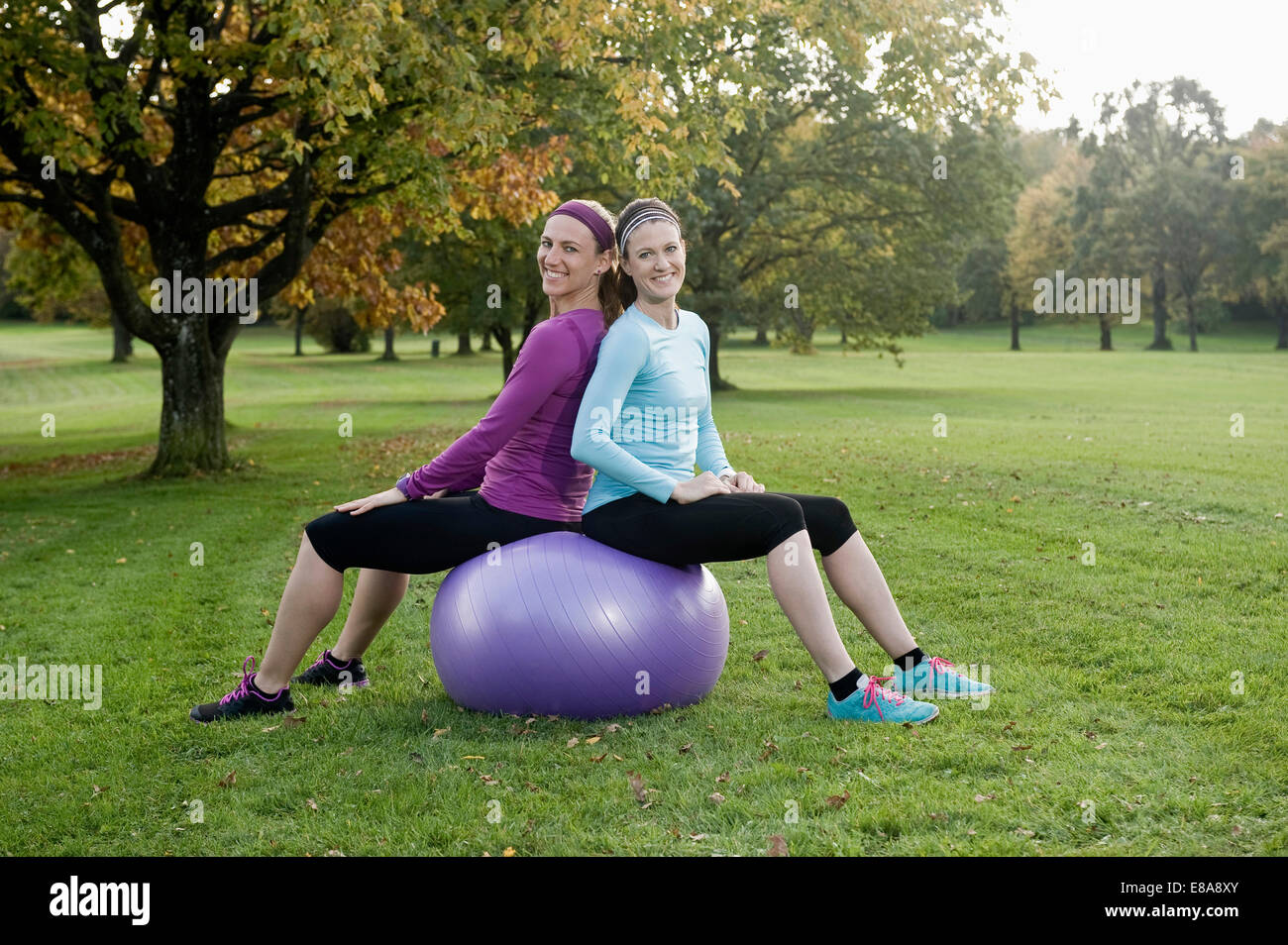 Women exercising in park with fitness ball, Woerthsee, Bavaria, Germany - Stock Image