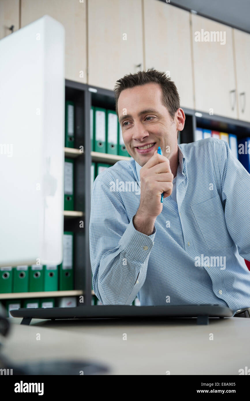 Young man sitting office working computer - Stock Image