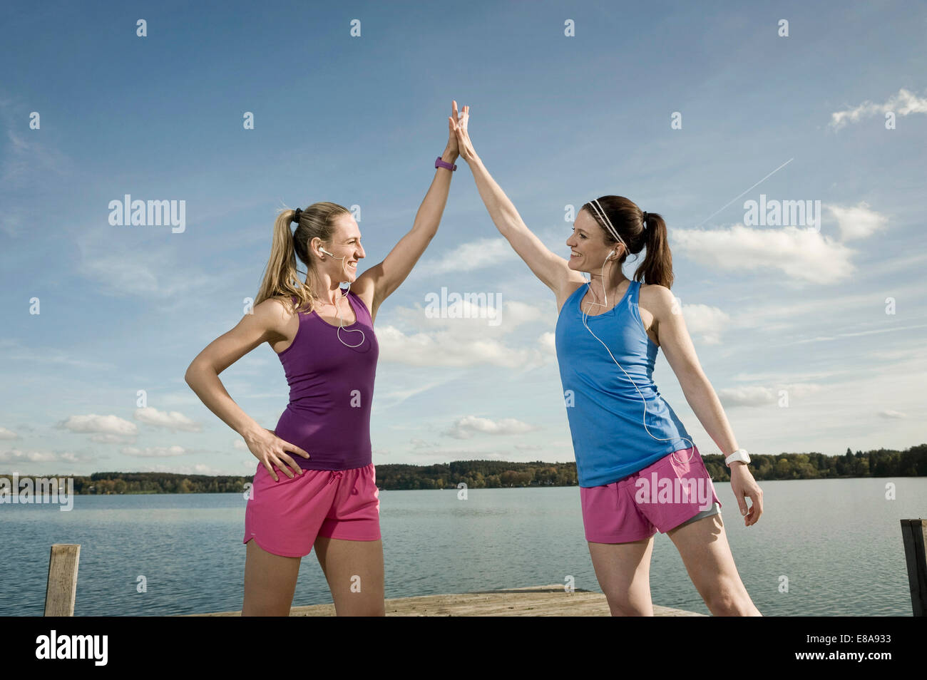 Jogging women giving high five, Woerthsee, Bavaria, Germany - Stock Image