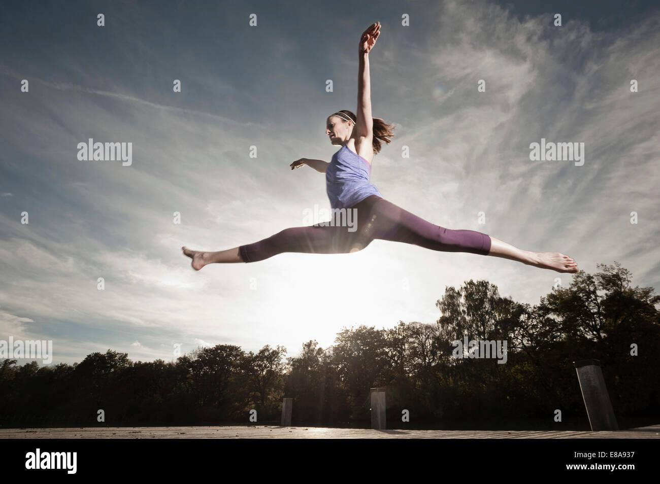 Woman jumpingmid air, Woerthsee, Bavaria, Germany - Stock Image