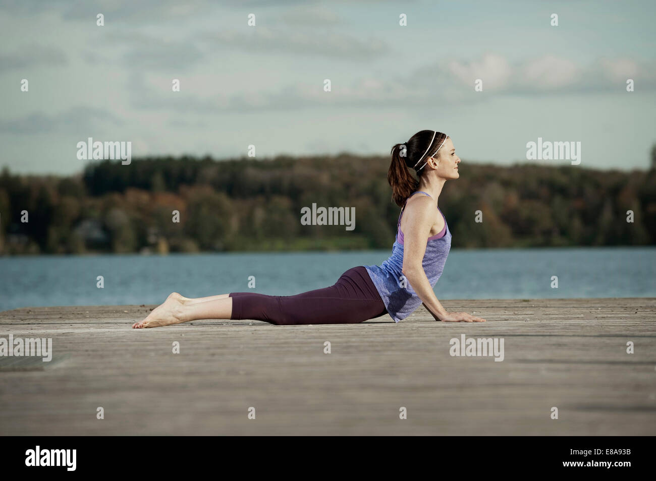 Woman practicing yoga on jetty, Woerthsee, Bavaria, Germany - Stock Image