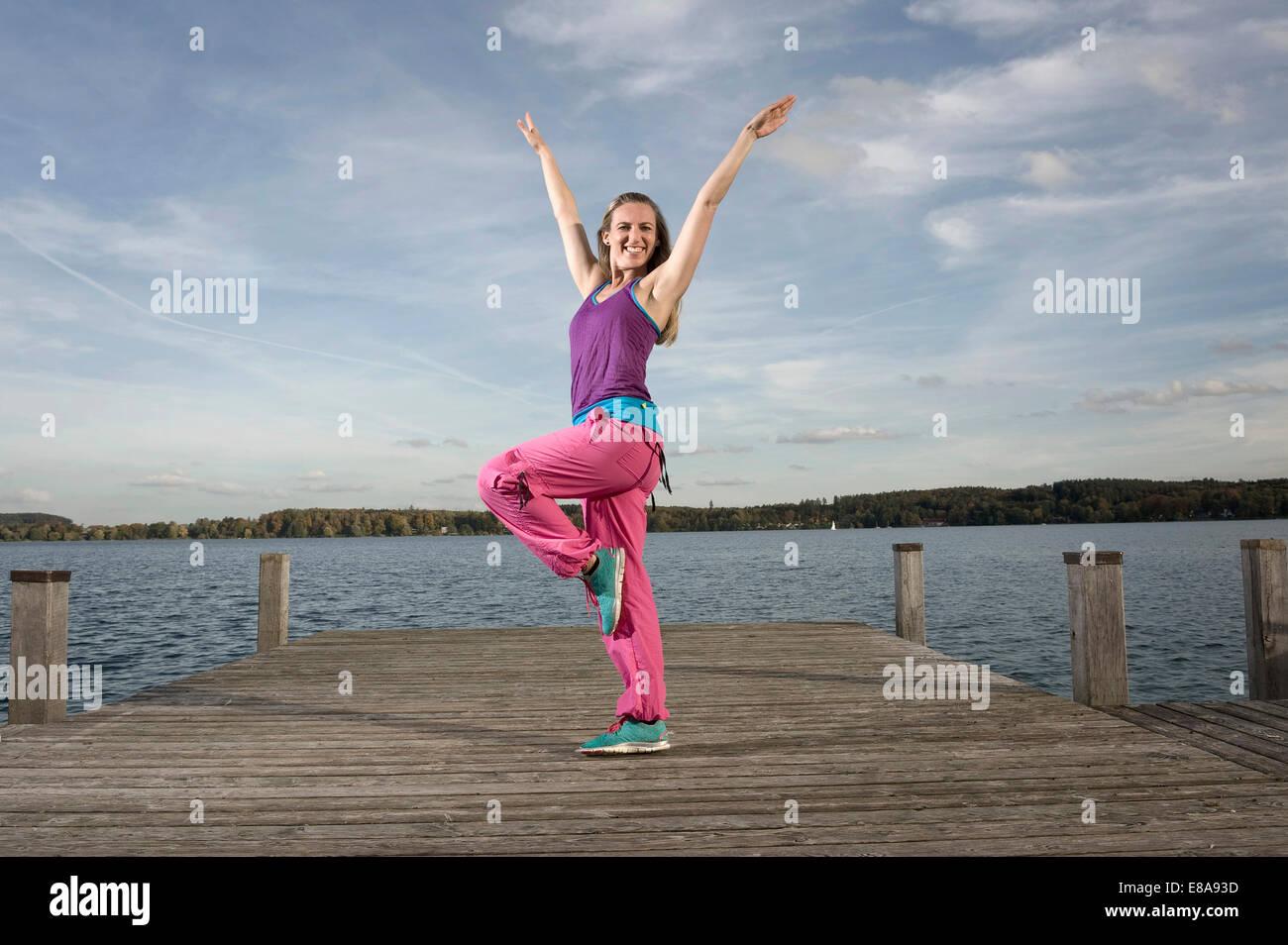 Woman dancing Zumba on jetty, Woerthsee, Bavaria, Germany - Stock Image