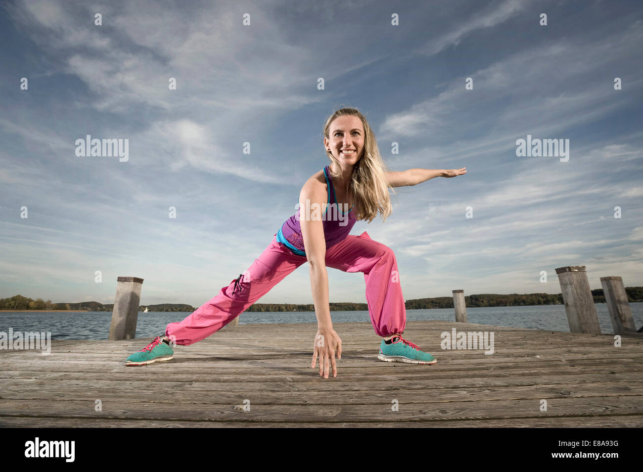 Woman dancing Zumba on jetty, Woerthsee, Bavaria, Germany - Stock Image