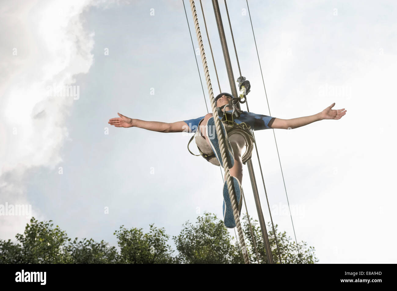 teenager balancing in a climbing crag - Stock Image