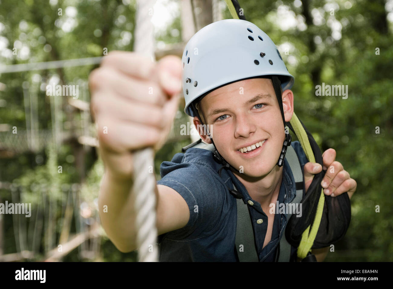 smiling teenager in a climbing crag, close-up - Stock Image