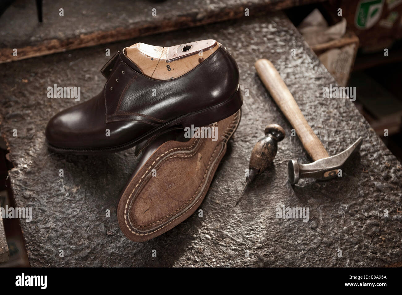 Pair of leather shoes, awl and hammer in a cobbler's shop - Stock Image