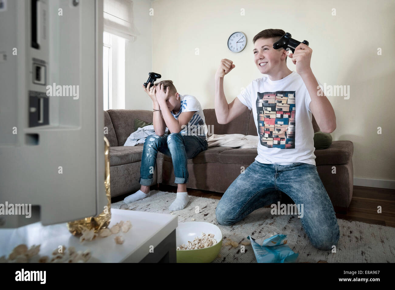 Two teenage boys playing video game - Stock Image