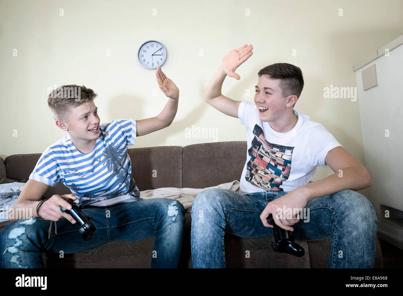 Two teenage boys with video game controllers high fiving - Stock Image