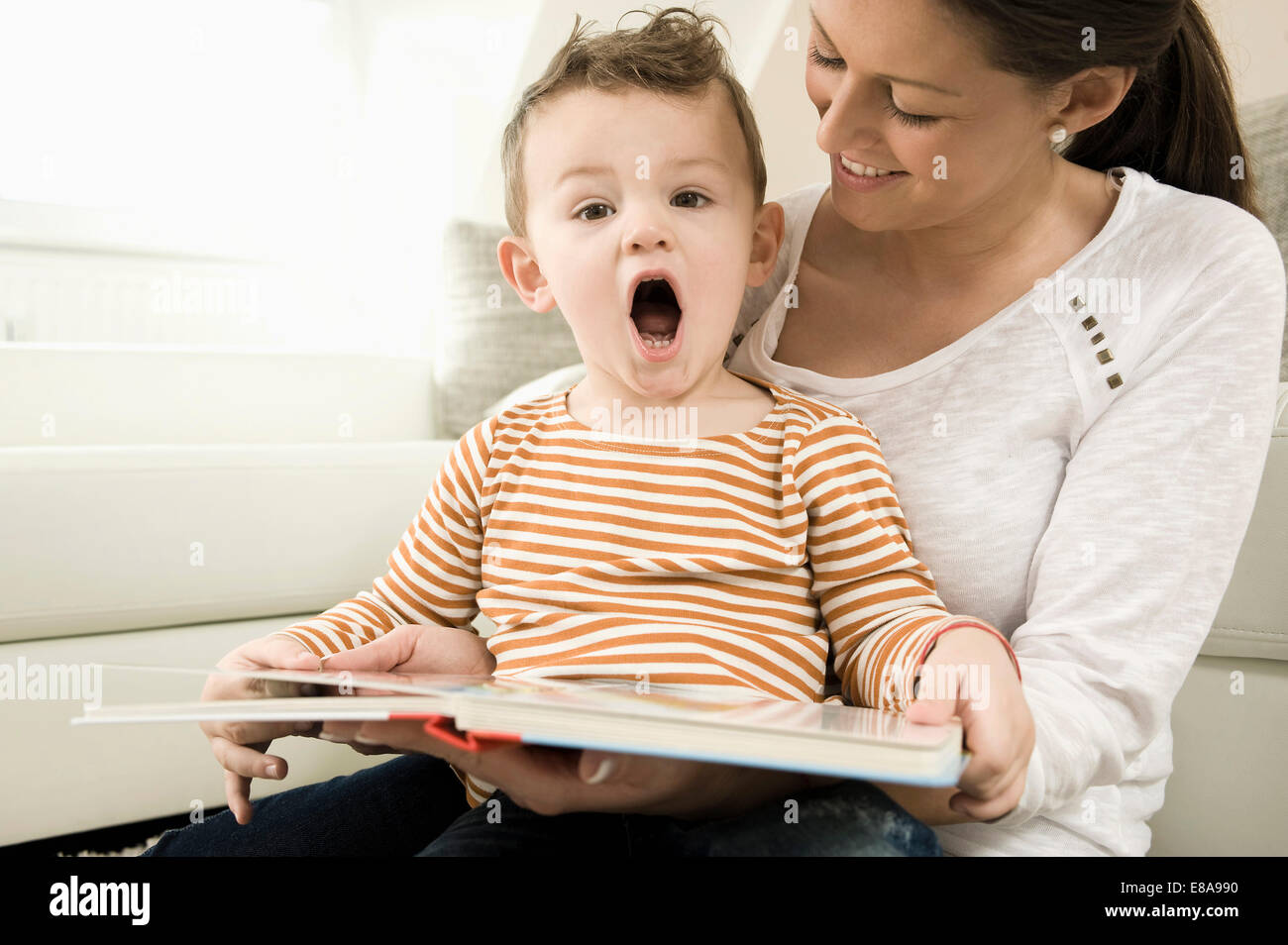 Mother and son are watching storybook, smiling - Stock Image