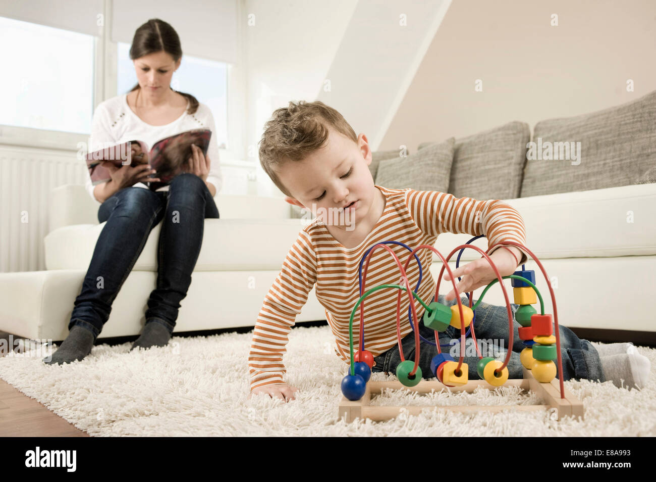Boy playing game while mother sitting on sofa - Stock Image