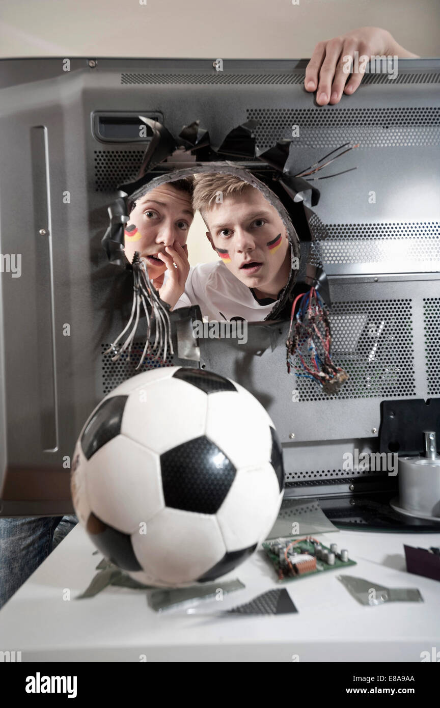 Two shocked teenage boys looking at soccer ball demolishing TV - Stock Image