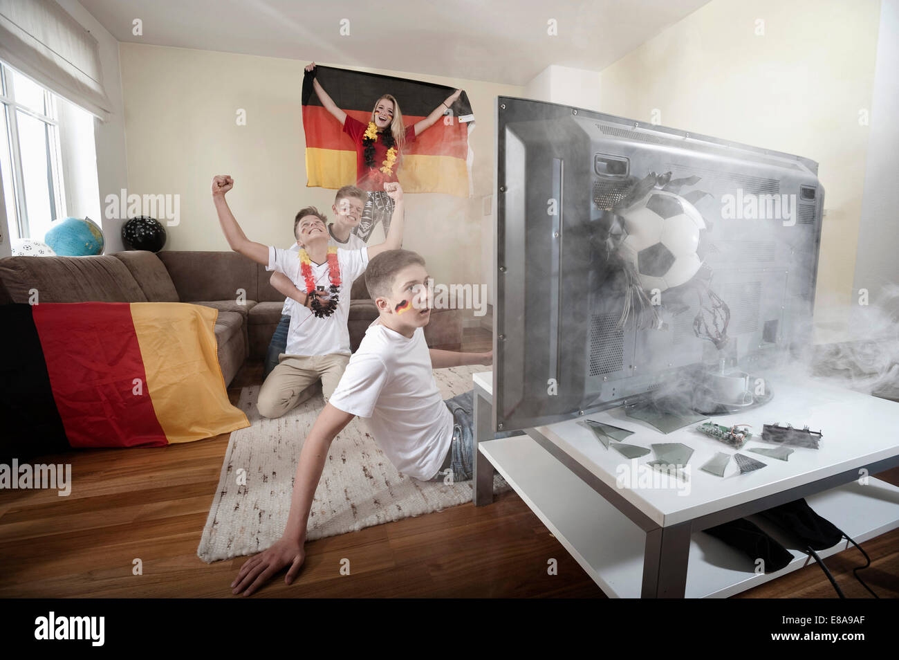Teenage soccer fans in living room with ball demolishing TV - Stock Image