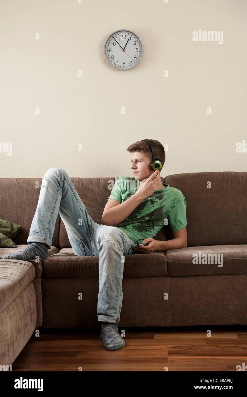 Teenage boy listening music at home - Stock Image
