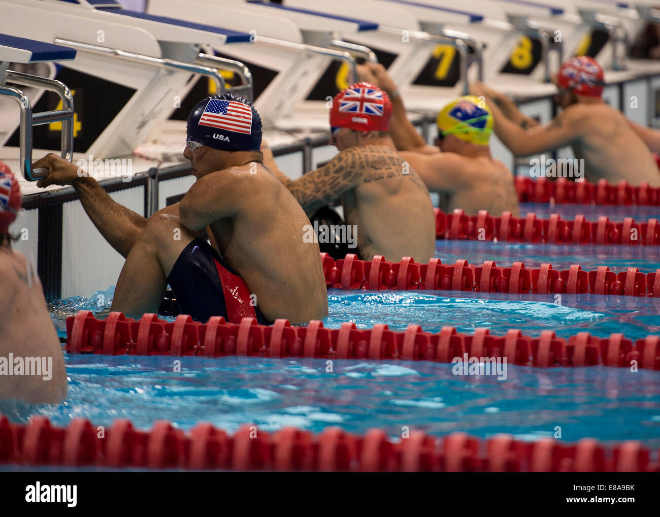 Retired U.S. Army Staff Sgt. Michael Kacer, left, prepares for the 50-meter backstroke race during the swimming - Stock Image