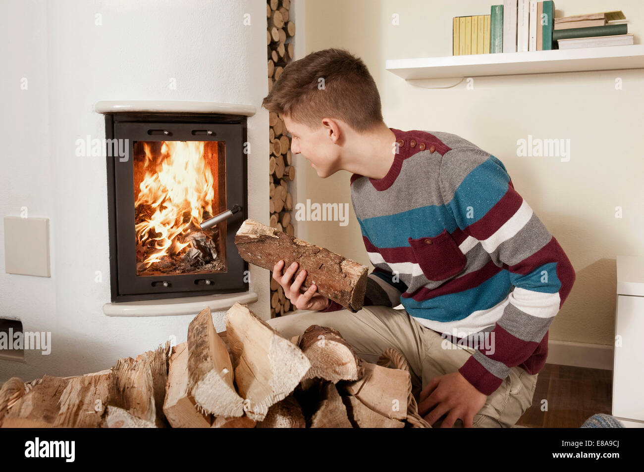 Teenage boy in front of fireside - Stock Image
