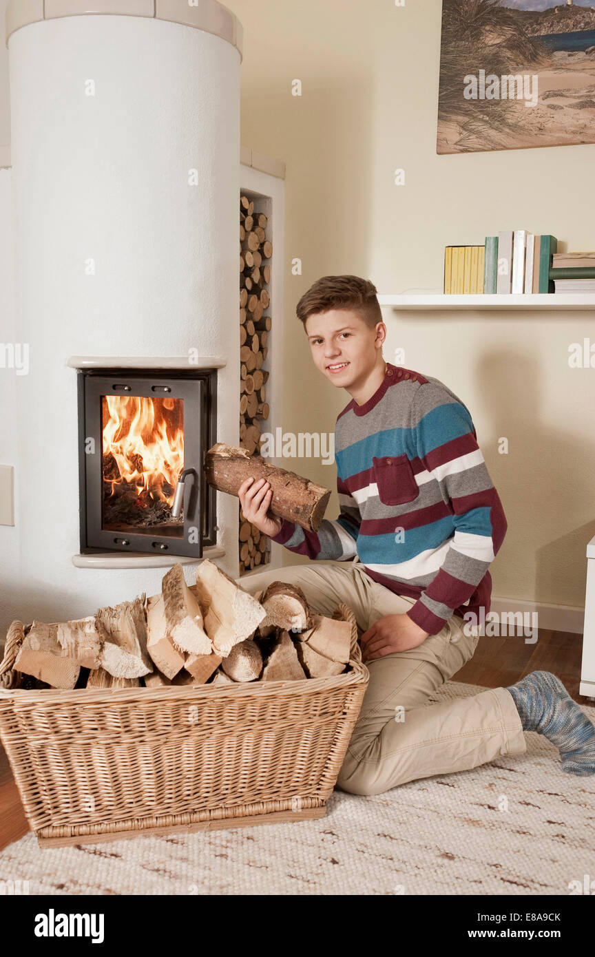 Teenage boy with log in front of fireside - Stock Image