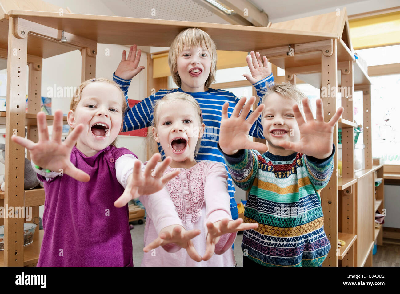 Four children with outstretched arms screaming - Stock Image