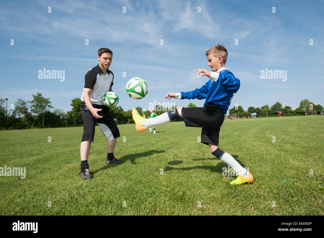 Soccer trainer teaching young player helping - Stock Image