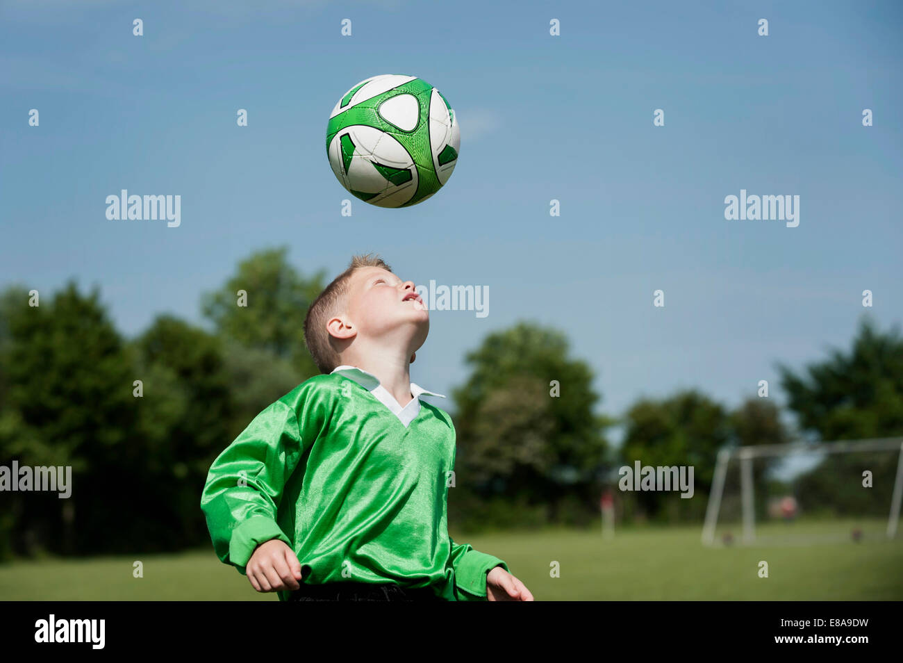 Young boy soccer practice football header ball - Stock Image