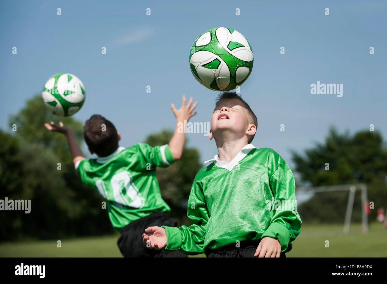 Two young football players learning ball control - Stock Image