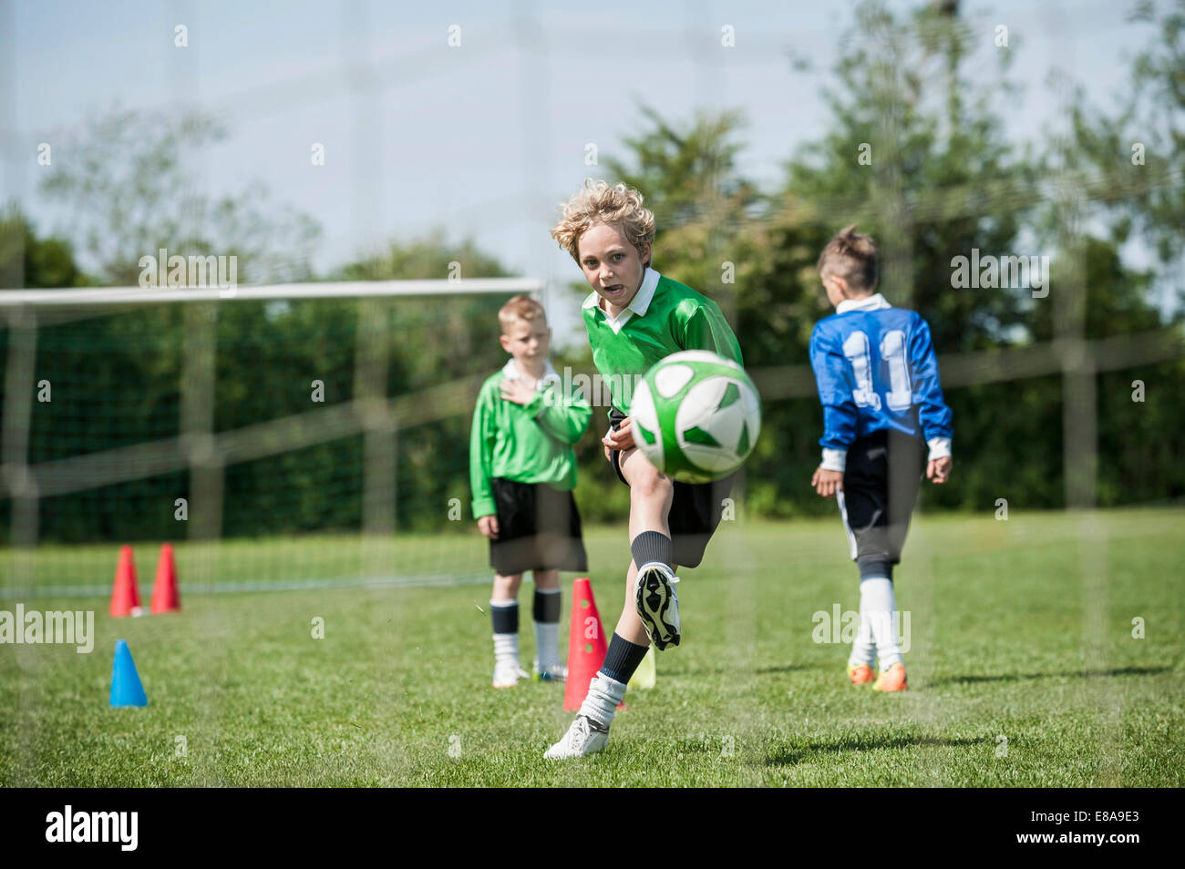 Boys junior soccer team practicing penalty - Stock Image
