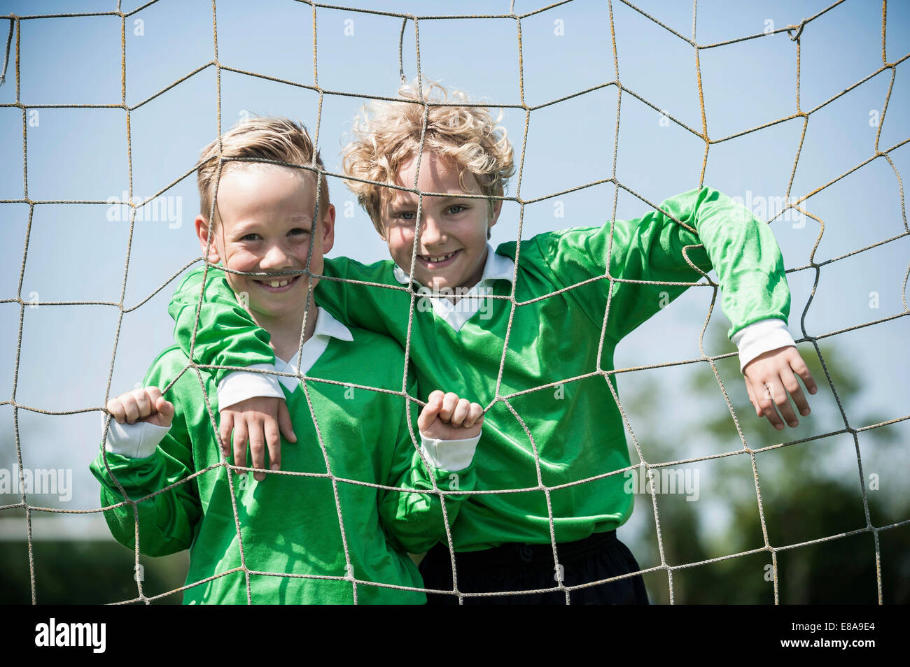 Two young football players posing in goal - Stock Image