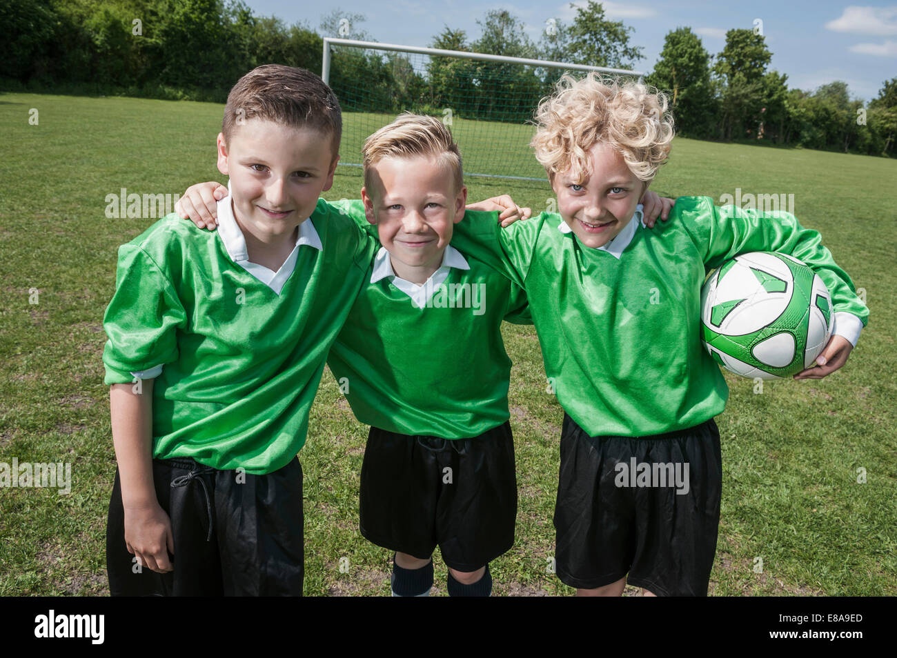 Three young soccer players posing portrait happy - Stock Image