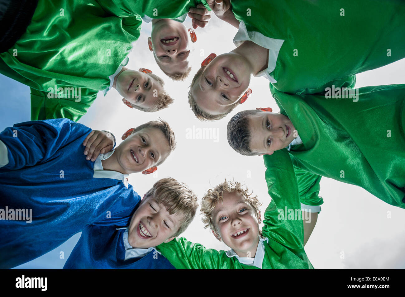 Junior soccer team in huddle circle from below - Stock Image