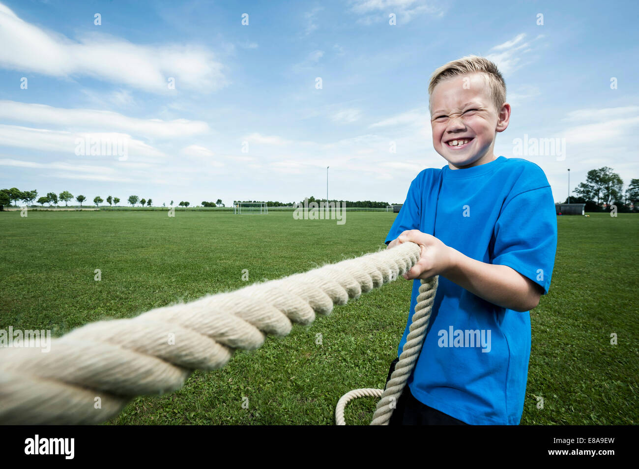 Young strong boy holding rope Tug-of-war strength - Stock Image