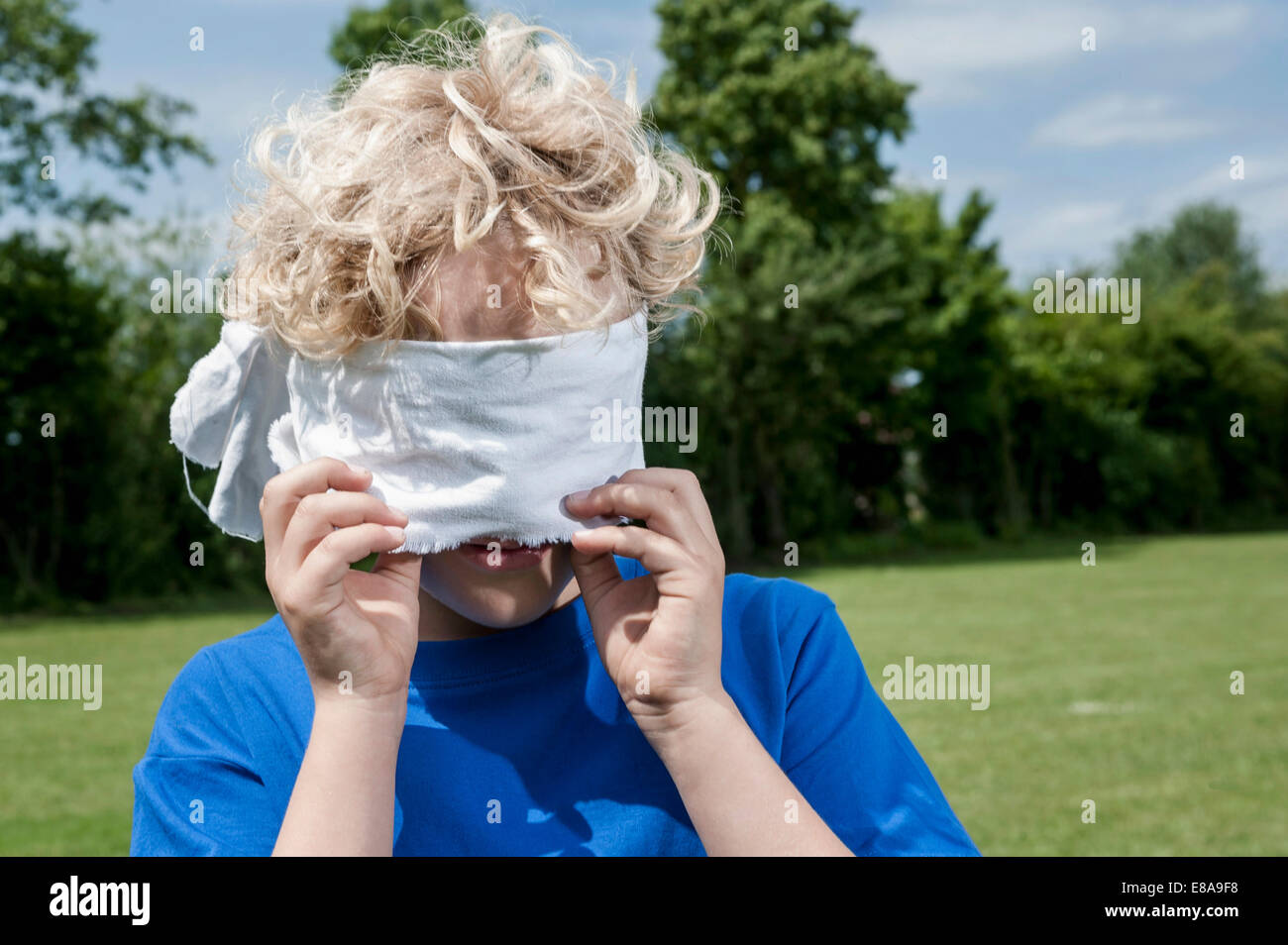 Young blonde boy holding removing blindfold - Stock Image