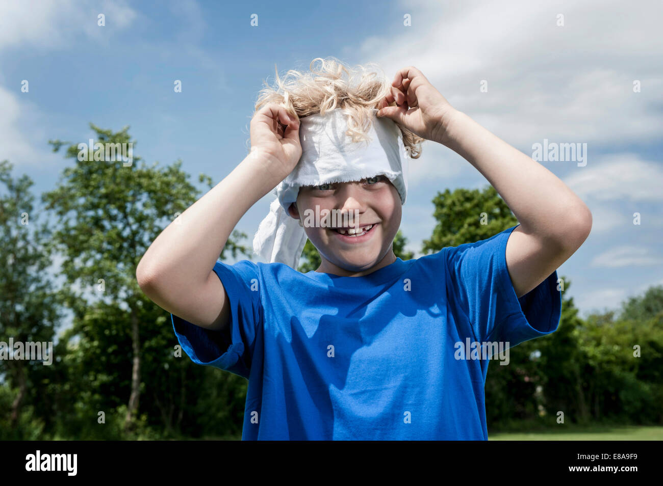 Young blond boy removing blindfold Stock Photo