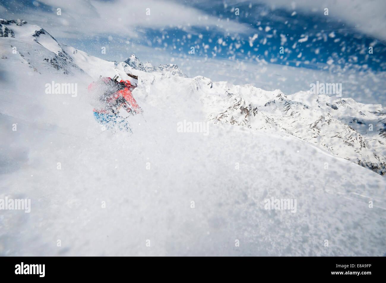 Skier woman downhill powder snow Alps - Stock Image