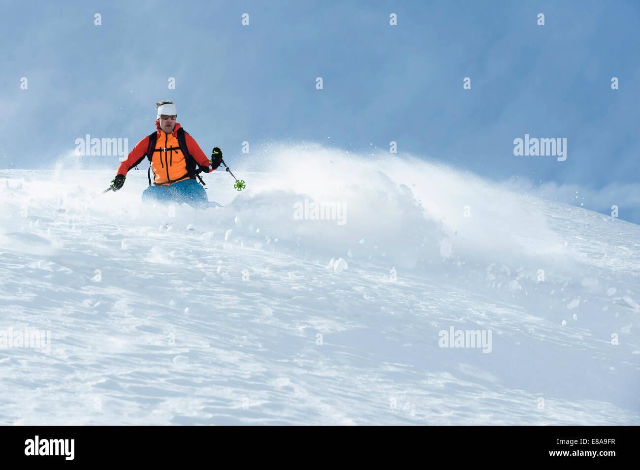 Man skiing downhill deep powder snow Alps - Stock Image