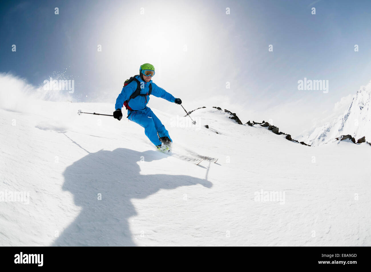 Man skier skiing downhill steep slope sunshine - Stock Image